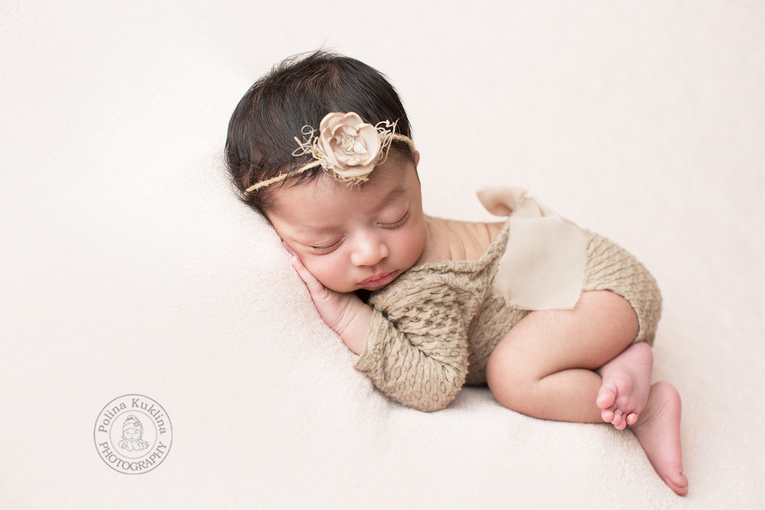 Newborn baby girl in a biege outfit