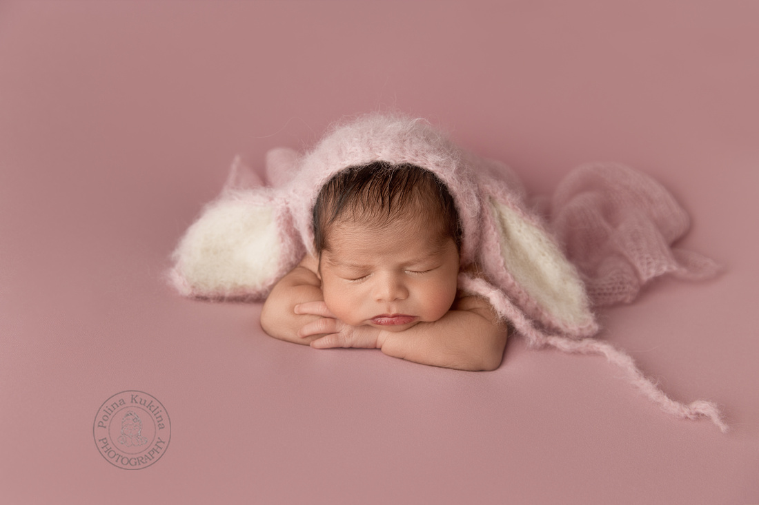 Beautiful newborn baby girl in a bunny bonnet posing newborns chin on hands pose