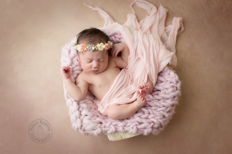 Newborn girl in a bowl